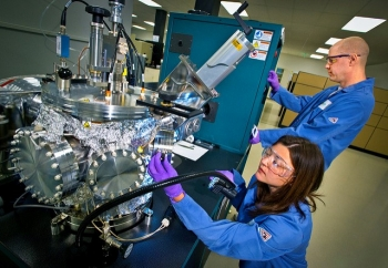 Female and male researchers conduct an experiment related to manufacturing