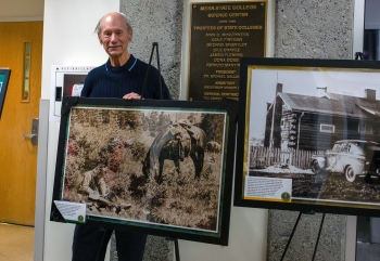 A former DOE geologist poses with his photo, which was taken in 1977.