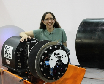 Heather Jones, a senior project scientist at Carnegie Mellon University, stands with one of the Radpiper robots.