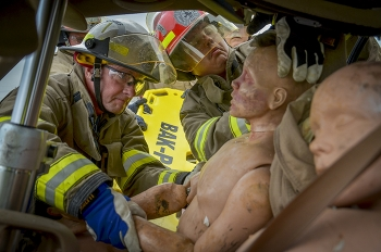 Fire Chief Darrell Howard, left, and Jake Mason stabilize rescue mannequins during a vehicle extrication simulation.