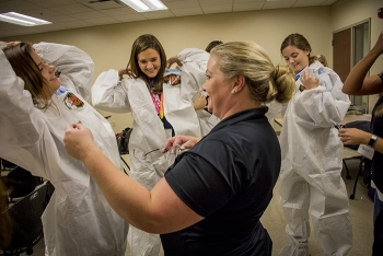 "Four Rivers Nuclear Partnership employee Elizabeth Wyatt teaches students how to ""don"" and ""doff"" personal protective equipment."