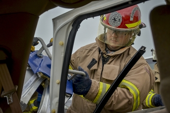 EM site worker Andrew Bachuss uses Jaws of Life to remove a vehicle door.