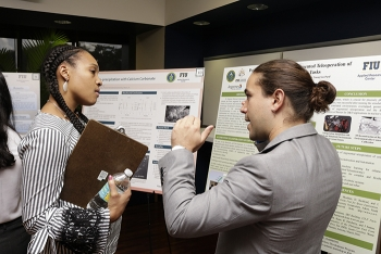 DOE Fellow Anibal Morales explains his research to EM Office of Technology Development Engineer Genia McKinley at the recent DOE Fellows Poster Exhibition and Competition.
