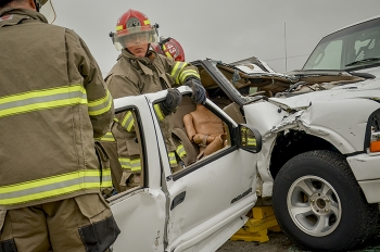 EM site firefighters access occupants trapped in a vehicle in a mock accident.