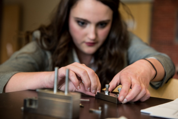 WSU student Jacqueline Reeve assembles an apparatus that bends the metal filament to hold samples for thermal ionization mass spectrometer analysis at PNNL.