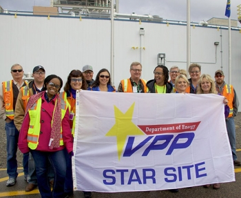 Fluor Idaho employees hold up their DOE Voluntary Protection Program flag.