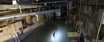 Workers deploy a robotic device to safely investigate and collect data from a potentially hazardous area of a former nuclear processing facility.