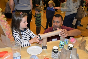 Sandia systems engineer Raheel Mahmood shows a student how to construct a roller coaster track for marbles.