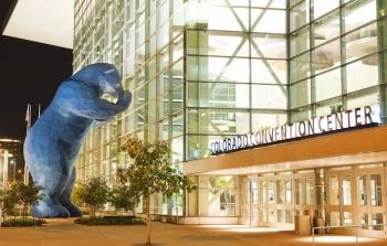 Image features the front entrance of the Colorado Convention Center and includes the sculpture of a giant blue bear peeking into the windows of the building.