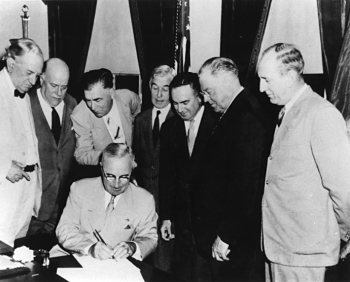 President Harry S Truman signs the Atomic Energy Act of 1946 establishing the U.S. Atomic Energy Commission.