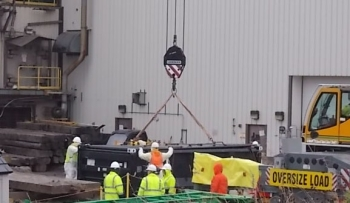 CHBWV crews use a large crane to load a section of a shield door from the site's vitrification plant during demolition activities.