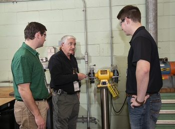 Savannah River Nuclear Solutions (SRNS) engineer Wim Lewis discusses safety requirements with SRNS employees Zach Bogard, left, and Wes McGuire, who are recent graduates of Murray State University.