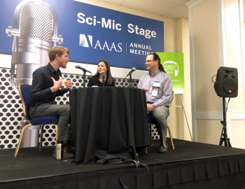 """Three people sit around a table with microphones in front of a backdrop that reads """"Sci Mic Stage AAAS Annual Meeting."""""""