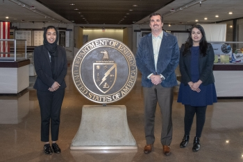 George Washington University graduate students Wardah Amir, left, and Mah-Noor Ahmed, right, with Program Manager Mark Scheuer at NNSA headquarters in Washington, D.C.