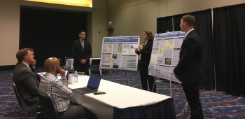 Three students stand next to two posters in front of a panel of judges.