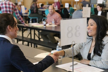 Jessica Esparza, a staffing specialist with MSA, right, assists a high school student with a mock interview and resume advice.