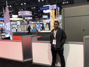 Student stands in front of industry booths at the AWEA WINDPOWER conference.