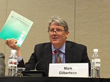 EM Principal Deputy Assistant Secretary Mark Gilbertson holds up the first Environmental Restoration and Waste Management Five Year Plan, a document from the earliest days of the Department of Energy cleanup program.