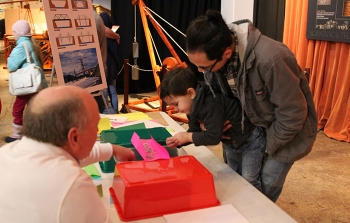 Concepts associated with bridge construction are tested by Liam Tom and his father Bryan under the watchful eye of electrical engineer Bill Reed.