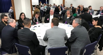 Attendees sitting around tables at the 2018 Champions Shared Lessons Learned Forum.