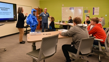 Instructor Billy Edington and an oral interpreter discuss how to don personal protective gear during the training.