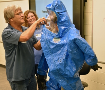 Classroom instructors Billy Edington and Pam Gray help a student put on personal protective gear correctly.