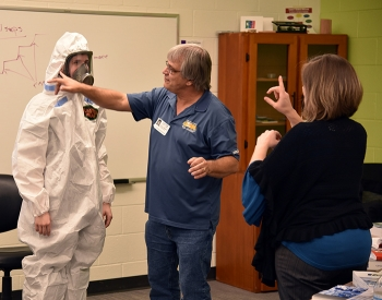 A student tries on a respirator with the help of instructor Billy Edington during the safety class.