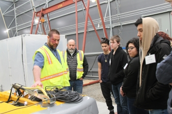 Hans Carman, left, and Matt Halsted with CH2M HILL Plateau Remediation Company show students equipment used at a Hanford Site mock-up. The recent tour highlighted the complexity of Hanford cleanup and allowed students to speak with professionals from a va