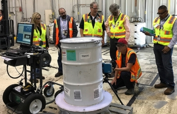 Workers with EM cleanup contractor Fluor Idaho test new technology for characterizing waste containers for the U.S. Environmental Protection Agency.