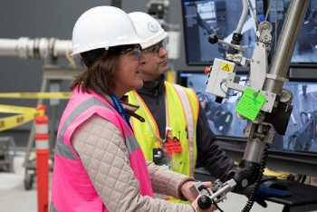 EM Assistant Secretary Anne White takes a hands-on approach at the 324 Building mock-up with assistance from operating engineer Warren Baze during her recent tour of the Hanford Site.