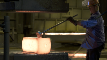A worker forges metal at a manufacturing facility.