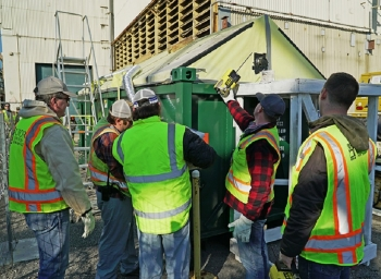 Employees with EM cleanup contractor UCOR install fogging equipment on a debris container at the Oak Ridge Site.