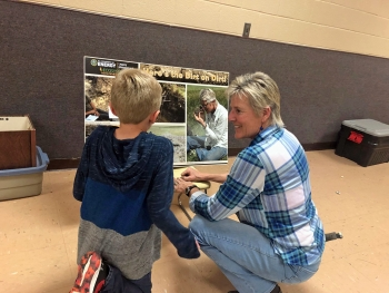 """Environmental scientist Marilyn Kastens shares """"Here's the Dirt on Dirt!"""" poster with a student."""