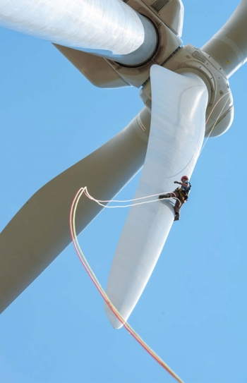 Large wind turbine blades and a man climbing one of the blades, with a rope dangling from beneath him.