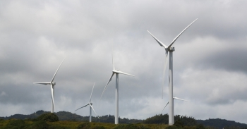 Five wind turbines at varying heights with clouds in the background.