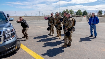 During the NNSA active shooter training exercise at the Hanford Site, an expert demonstrates using a patrol vehicle's engine block as effective cover.
