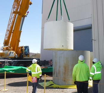 Using a 200-ton crane, workers return a waste container to its exterior steel shield at its new location at an outdoor storage area.