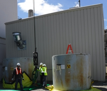 A crew safely finishes relocating two waste containers to their new location at an outdoor storage area.
