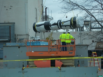 CH2M HILL BWXT West Valley workers remove a 900-pound section of the ventilation exhaust cell duct from the roof of the Main Plant Process Building in November 2018.