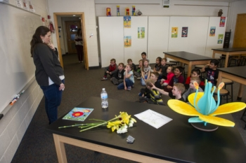 Runcorn's second grade class gathers to name the parts of a flower.