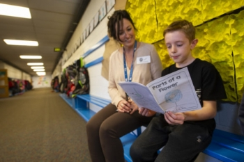 "A Temple View student shows his ""Parts of a Flower"" journal to INL's Jennifer Jackson."