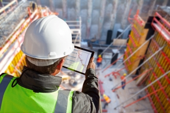 Man in a hard hat standing on top of a building, holding an e-tablet, with a view at construction workers doing work below.