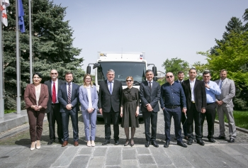 Georgia's Deputy Minister of Environment Protection and Agriculture and the head of Georgia's Agency of Nuclear and Radiation Safety are joined by U.S. and U.K. partners in front of the secure truck.