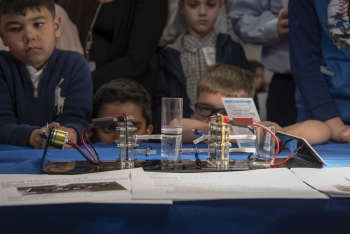 Children watch as a fuel cell turns hydrogen into energy.