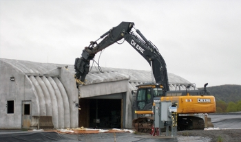 Demolition equipment takes the first bite out of a facility housing a liquid pretreatment system at EM's West Valley Demonstration Project.