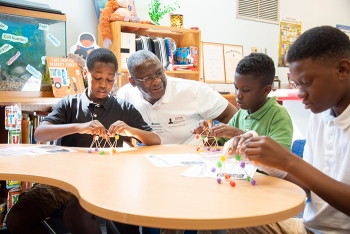 Thomas Johnson, deputy manager of DOE-Savannah River, helps a fourth-grade class at Mary Ford Elementary School create geometric domes out of gum drops.