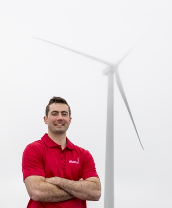 A student in a red shirt stands in front of a wind turbine on a cloudy day.