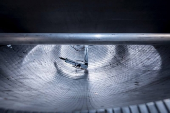 View of the ultracold neutron trap, comprising 5,139 permanent magnets arranged in an asymmetric bowl-shaped array, during magnetic field mapping with a robotic arm.