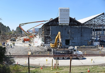 Oak Ridge Site workers remove asbestos-containing panels from portions of the K-1037 Building while demolition and debris removal are underway on other sections.