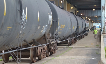 A deactivation worker inspects railcars containing insulating oil from the Paducah Site's C-533 Switchyard as they are prepared to be shipped to a buyer for the Paducah Area Community Reuse Organization.